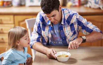 Isä muussaa ruokaa lapselle